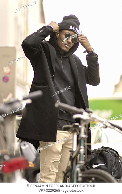 stylish man between bicycles wearing black hoodie and coat, streetstyle clothes, in Munich, Germany