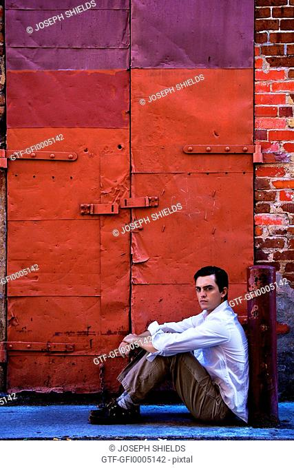 Young man sitting in alley, staring belligerently at the camera