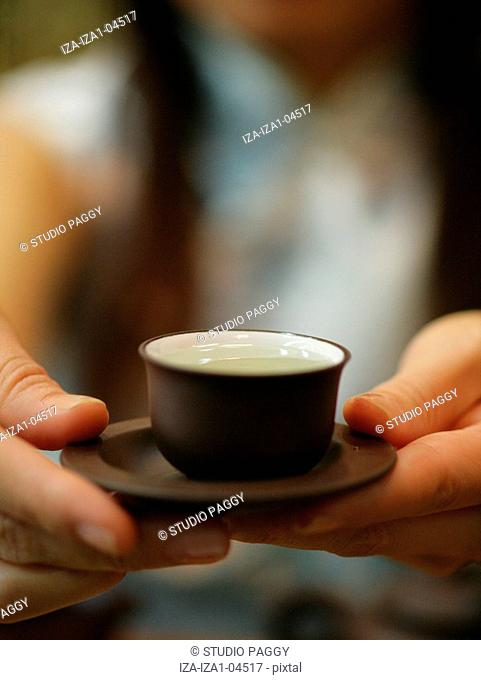 Close-up of a person's hand holding a cup of tea with a saucer