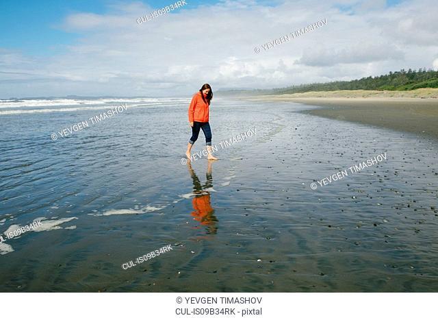 Young woman walking barefoot on beach, Long Beach, Vancouver Island, British Columbia, Canada