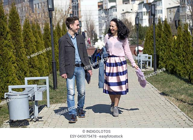 Mother and son are together. Couple strolling in the park near a fountain