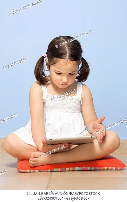 Little girl sitting on her room floor using tablet computer