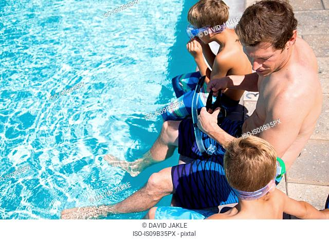 Man and two sons sitting on poolside in scuba goggles, Laguna Beach, California, USA