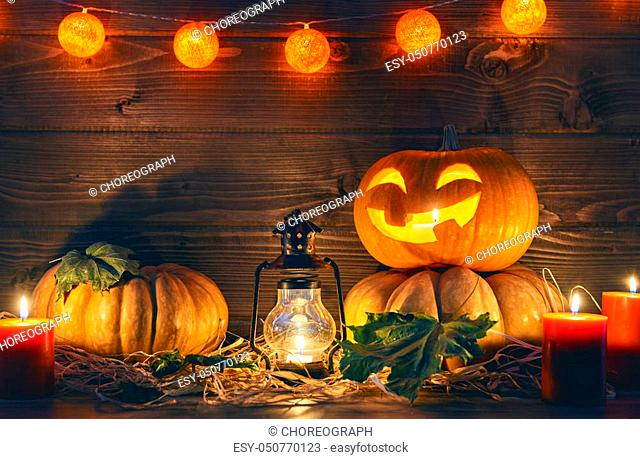 Happy halloween! Head pumpkin, candles and autumn leaves on wooden background