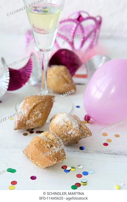 Mutzen (carnival pastries) with confetti, balloons and sparkling wine