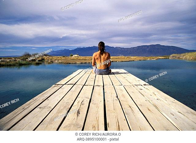 A man sitting at the end of a dock in Cuatro Cicnigas, Mexico
