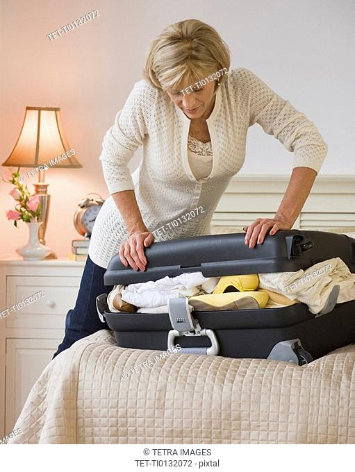 Woman packing full suitcase
