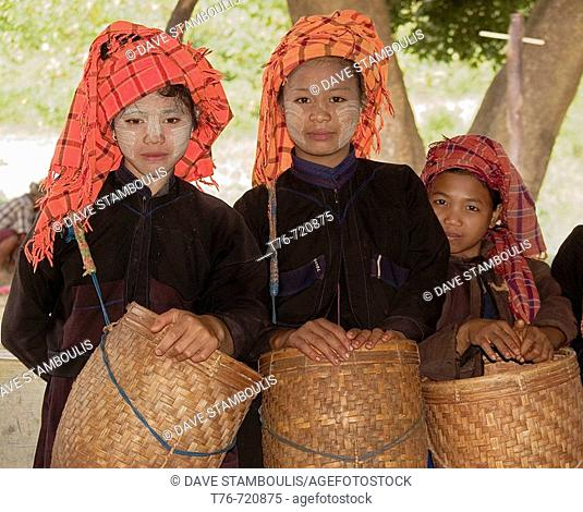 Three Pa O hilltribe girls with bamboo baskets for work at Inle Lake in Myanmar