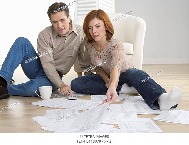 Couple with paperwork on floor