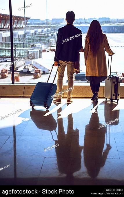 Business couple holding luggage while looking through window at airport departure area