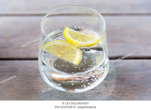 drink and refreshment concept - glass of sparkling water with lemon slices on table
