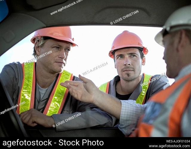 Male architect explaining construction workers while sitting in truck