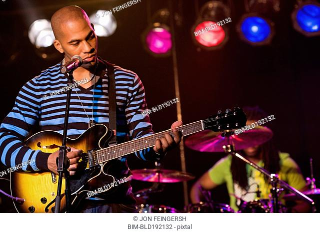 African man playing electric guitar onstage