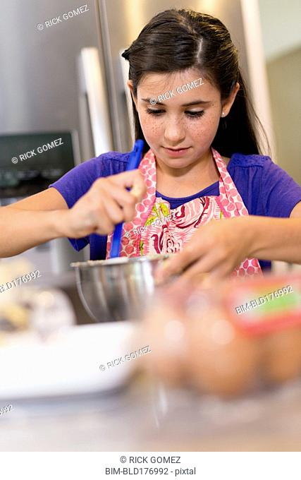 Mixed race girl baking in kitchen