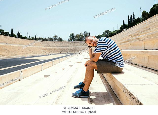 Greece, Athens, man sitting in the stands of the Panathenaic Stadium