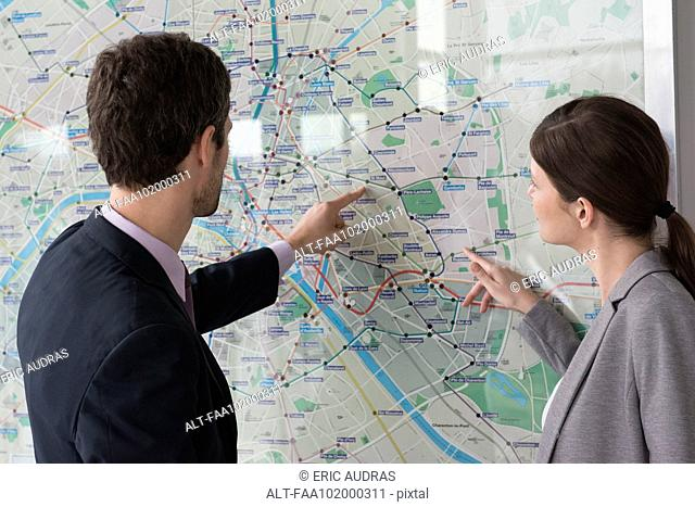 Man and woman looking at Paris metro map together