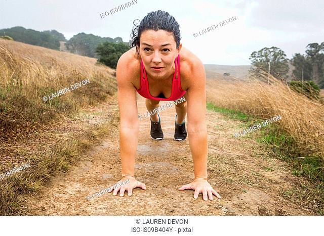 Mid adult woman training, doing push ups on dirt track