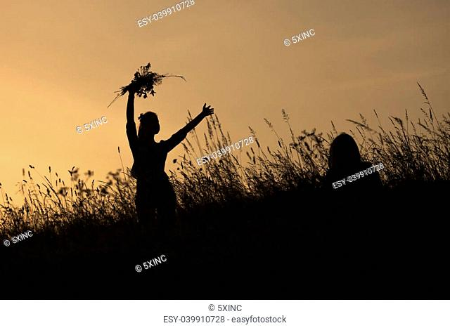 Silhouettes of happy girl picking flowers during midsummer soltice celebraton against the background of sunset