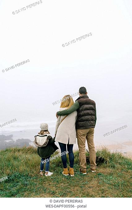 Family with dog at the coast on a foggy winter day looking at view