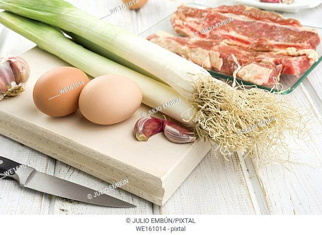 raw meat vegetables and eggs, on white wood