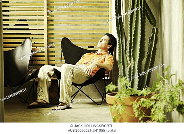 Side profile of a mature man sitting on a chair and sleeping