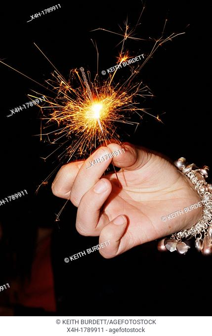 Girl's hand holding a mini sparkler, Wales