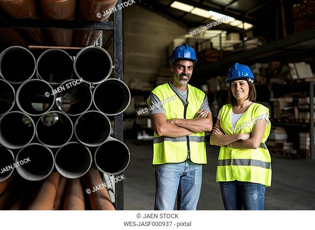 Construction workers standing in warehouse next to stack of pipes with arms crossed