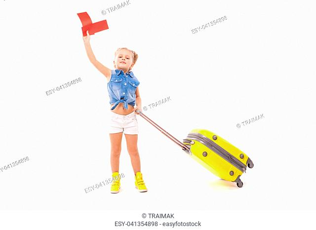 Isolated on white, cute little caucasian blonde girl in blue shirt, white shorts, sunglasses and yellow boots hold yellow suitcase by the handle, look at camera
