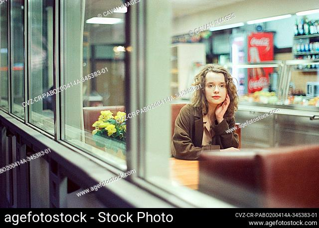 A woman is sitting at the train station