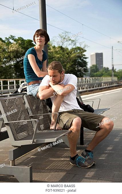 A bored backpacker couple waiting for their train on a train platform