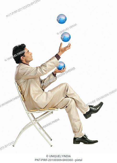 Businessman sitting on a chair and juggling globes