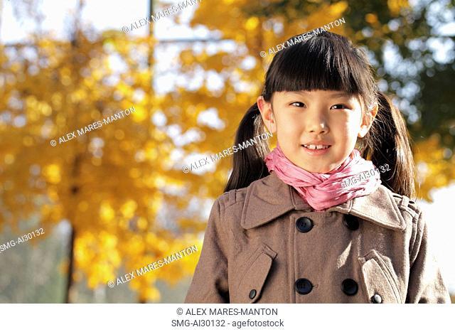 Head shot of young girl wearing a coat outdoors