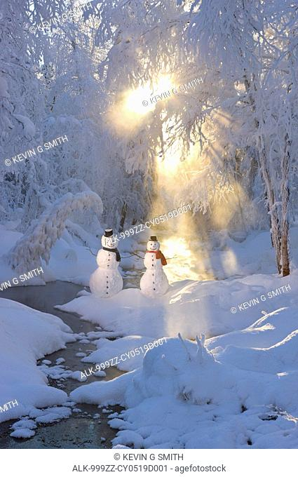 Snowman couple standing next to a stream with sunrays shining through fog and hoar frosted trees in the background, Russian Jack Springs Park, Anchorage