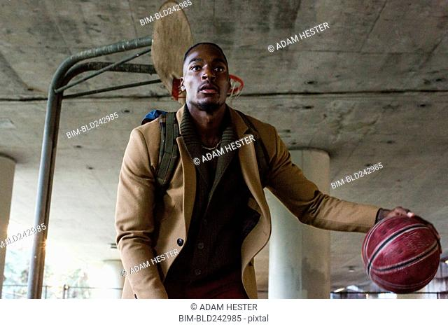 Black man wearing backpack playing basketball under overpass