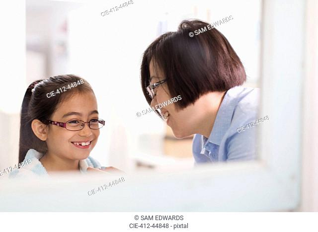 Reflection of mother and daughter in bathroom mirror