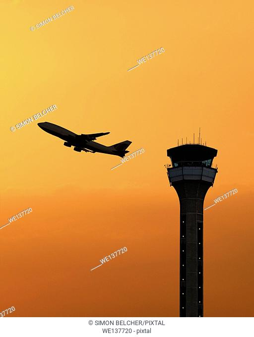 Air traffic control tower with a plane taking off at sunset. Luton Airport, UK
