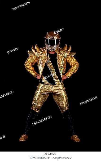 Strong guy posing in golden costume for performance, isolated on black