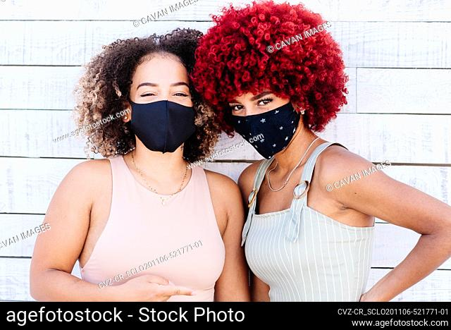 Two latin women with mask in a carefree attitude on a white background