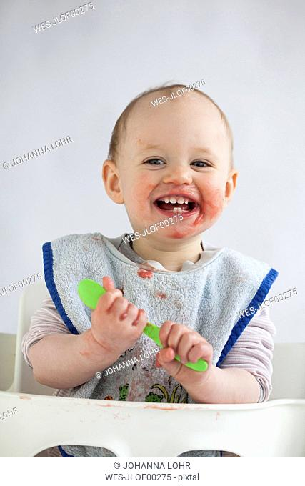 Portrait of happy baby girl with smeared face on high chair
