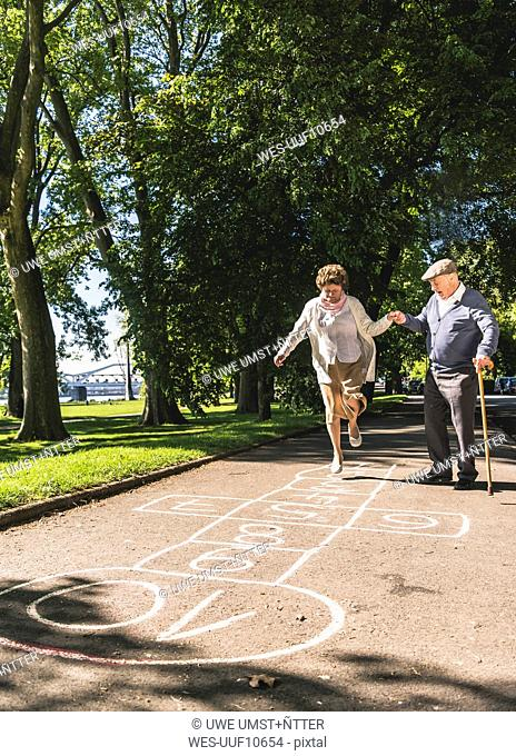 Senior woman playing hopscotch while husbanf watching her