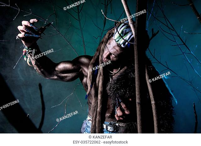 Muscular werewolf with dreadlocks with long nails among the branches of the tree. Gothic image of scary diabolical creatures for Halloween
