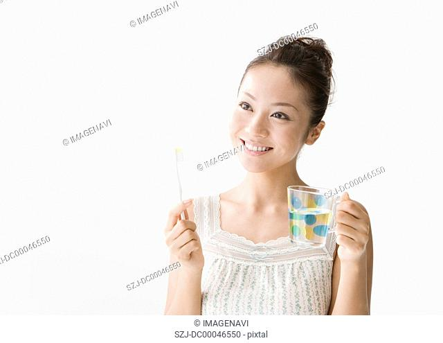 Woman holding toothbrush and cup