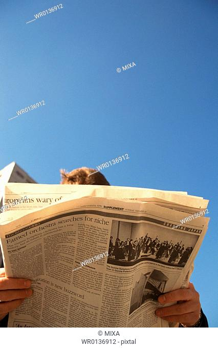 Low angle view of a person reading newspaper