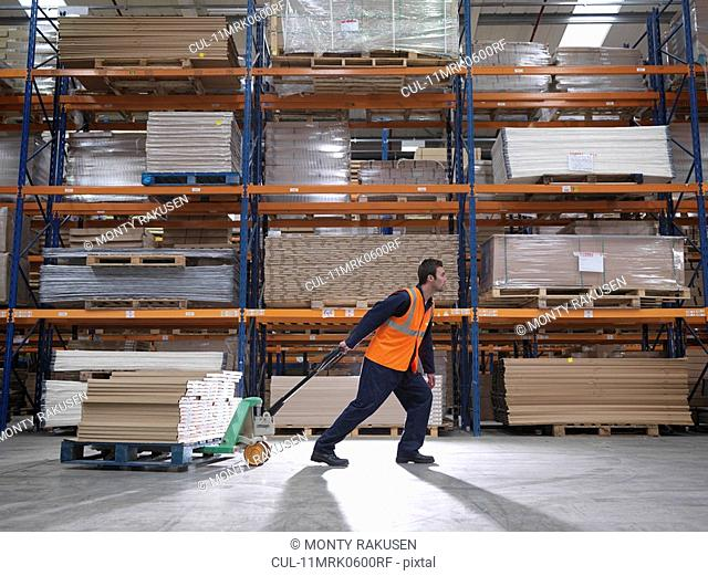 Worker Transporting Product In Warehouse