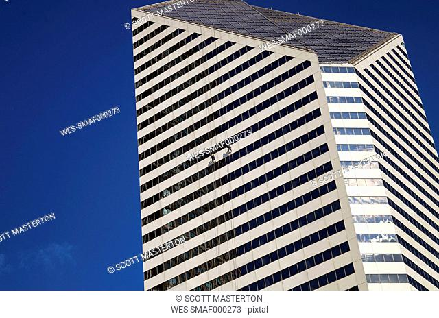 USA, Illinois, Chicago, two window cleaners hanging at facade of skyscraper