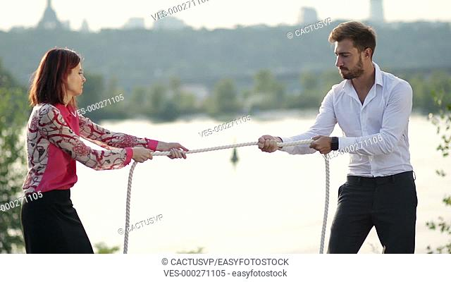 Business partners playing tug of war outdoors