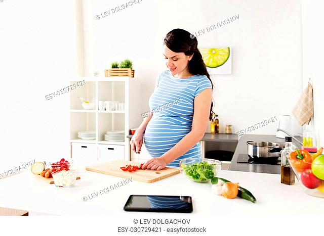 healthy eating, pregnancy and people concept - pregnant woman cooking and chopping cherry tomatoes at home kitchen