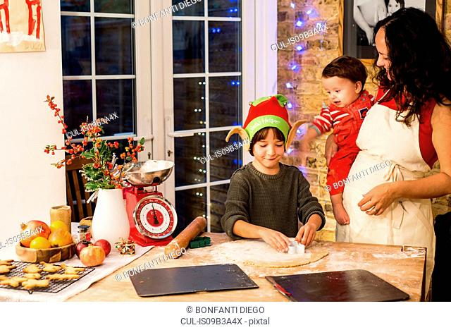 Mature woman preparing Christmas cookies with sons at kitchen counter