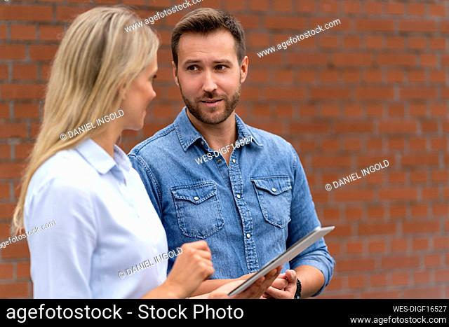 Business professionals with digital tablet having discussion in front of wall