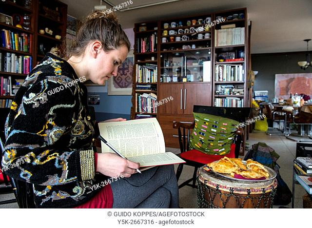 Newark, New Jersey, USA. Young brunette woman reading a book, while sitting in a living room